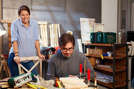 tinkering: Tinkering couple working in workshop.