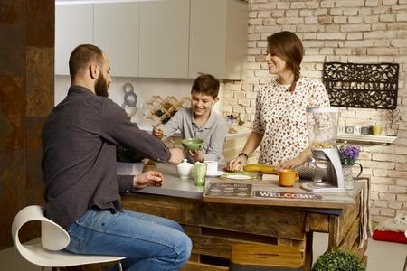 white kitchen: Happy family having breakfast in the kitchen. Stock Photo