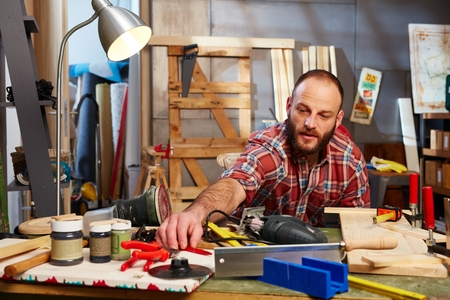 tinkering: Busy man tinkering in workshop. Stock Photo