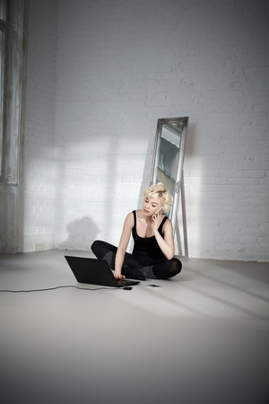 tailor seat: Blond female dancer sitting on floor in ballet studio, using mobilephone and laptop computer.