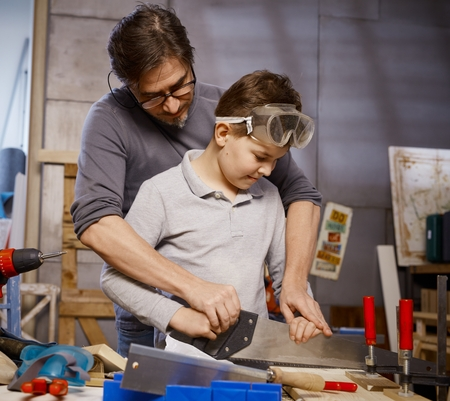 Father teaching son to use saw in workshop. photo