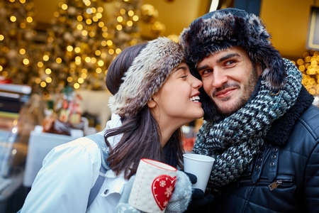 Loving couple kissing and having hot drink on the street at wintertime.