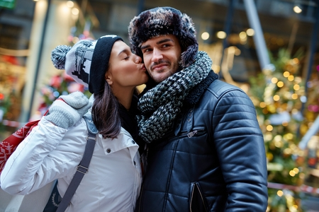 be kissed: Young couple kissing at wintertime outdoors doing christmas shopping.