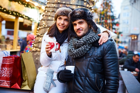 Young couple doing christmas shopping in christmas fair, drinking hot drinks, embracing.