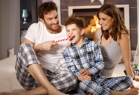 nighty: Young family with little boy having fun with lollipop in the morning.