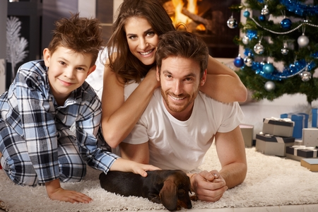 nighty: Happy little family playing on floor with newly received puppy at christmas time. Stock Photo