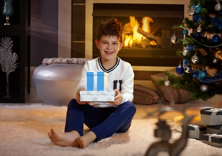 Happy boy smiling, holding christmas present, sitting on floor by christmas tree. Stock Photo