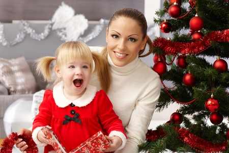 Happy little girl holding christmas surprise sitting by christmas tree with mother. Stock Photo
