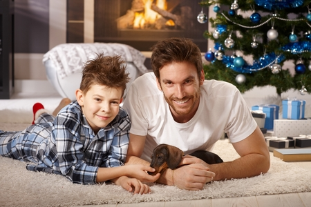 nighty: Happy young father and son lying on floor at christmas time, playing with adorable dachshund puppy received for christmas.
