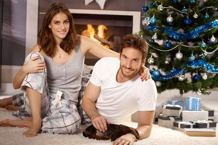 Happy attractive young couple caressing sleeping dachshund puppy at christmas morning. Stock Photo