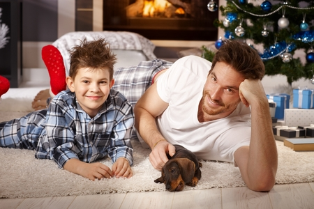 Young father playing with son and puppy on floor by christmas tree.