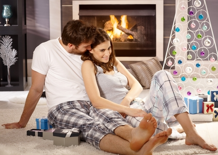 Loving young couple sitting on floor by christmas tree at christmas morning, caressing. Stock Photo
