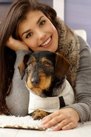 Closeup portrait of beautiful young woman hugging dog, smiling happy, looking at camera.
