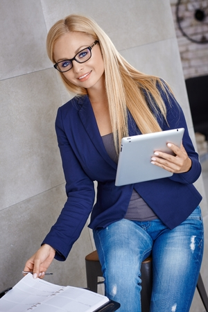 Happy young businesswoman working , using tablet and personal organizer, smiling, looking at camera. photo