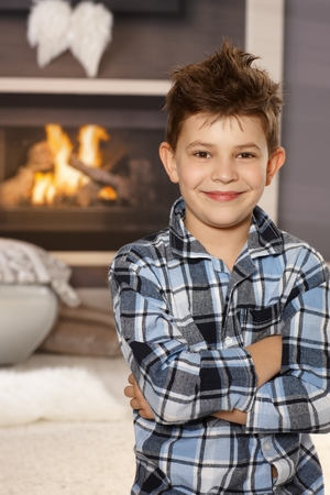 Confident happy little boy standing arms crossed in living room, smiling, looking at camera.