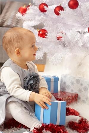 Little girl sitting under christmas tree, opening present.