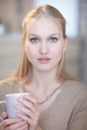 Portrait of innocent looking nordic woman holding tea mug, looking at camera, blue eyes.