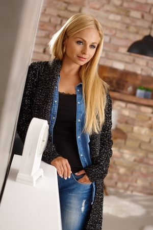 Thoughtful young blonde woman standing against wall. photo