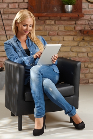Blonde woman using tablet pc at home, smiling, sitting in armchair.