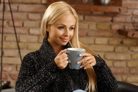 Beautiful blonde woman holding a mug of tea, smiling. photo