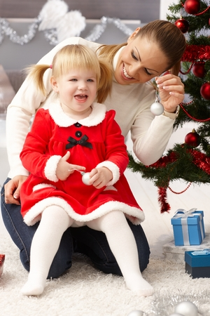 Mother and daughter smiling happy at christmas eve, holding ornaments. photo