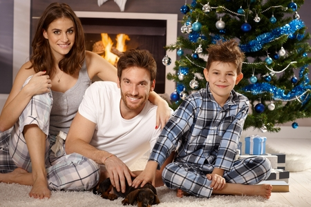 Happy young family with little boy and dachshund puppy, sitting on floor at christmas morning, playing with puppy, smiling. photo