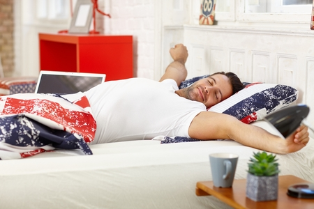 stubbly: Young man waking up in the morning, stretching in bed.