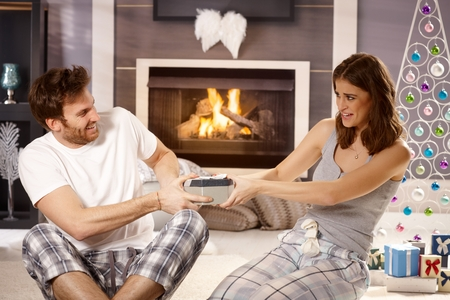 Young couple pulling about christmas present, having fun. photo