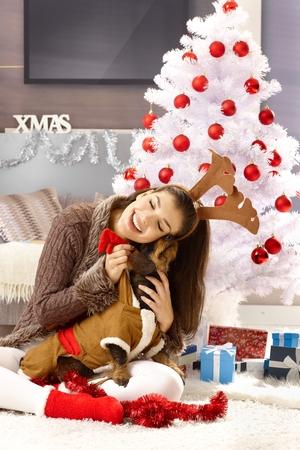 Happy woman hugging dog, sitting on floor by christmas tree.