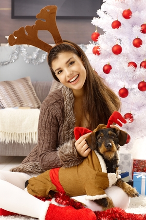 Young woman playing with dog at christmas, smiling happy. Stock Photo