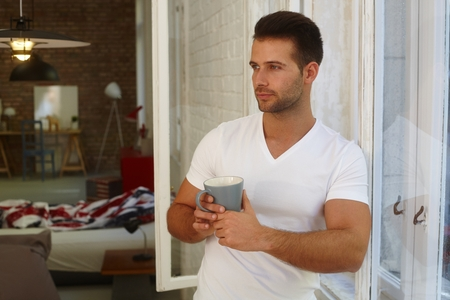 fantasize: Handsome young man holding tea mug, daydreaming at home.