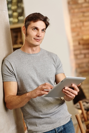 fantasize: Casual man holding tablet computer, thinking, looking away.