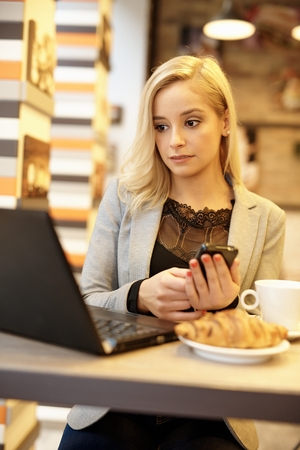 Young woman using laptop computer and mobilephone while having croissant.