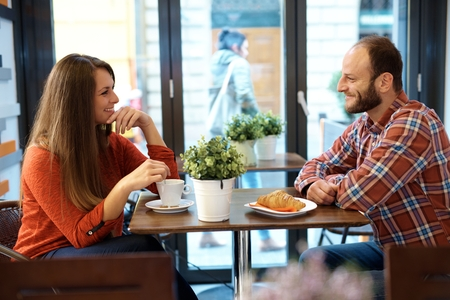 Happy couple sitting and chatting in cafe, drinking coffee, having croissant.