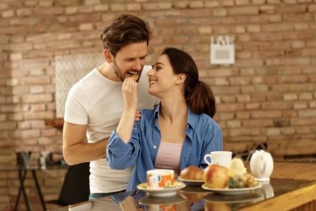 hombre comiendo: Feliz pareja romántica de desayunar juntos, alimentación de los demás. Foto de archivo