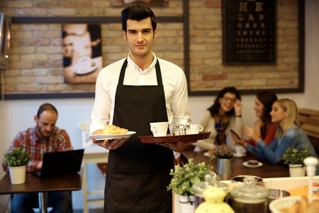 male hand: Handsome waiter working in cafeteria, holding trays in both hands, looking at camera,