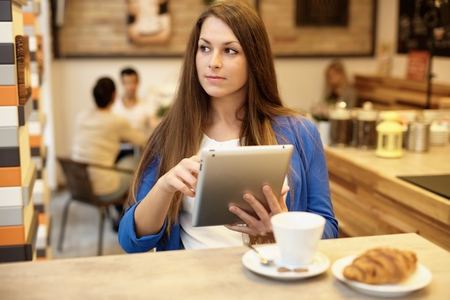 Attractive young woman using tablet computer in cafeteria, looking away.