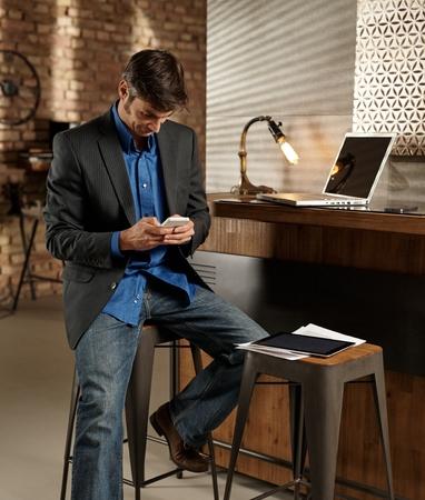 barstool: Businessman using mobilephone, sitting on barstool.