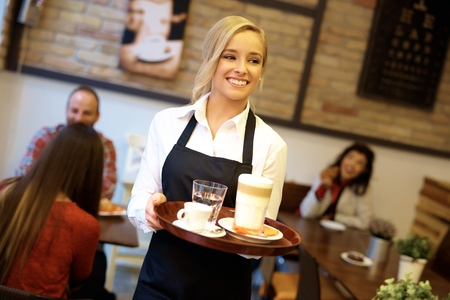 Happy blonde waitress holding tray, working in cafeteria. Archivio Fotografico