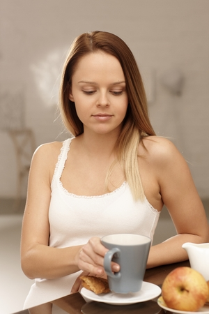 Young woman having breakfast at home. photo