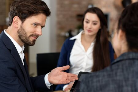 teamworking: Closeup portrait of businessman talking to colleagues, using tablet.