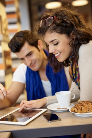 Young couple using tablet, smiling happy.