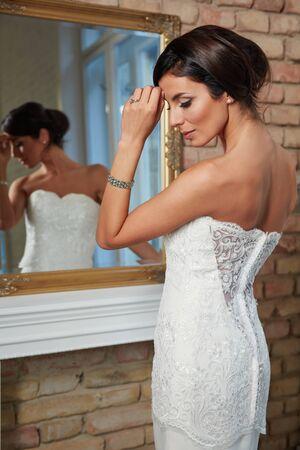 mirror: Pretty bride posing front of mirror.