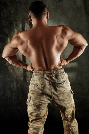 Male bodybuilder flexing back muscles with bare upper body.