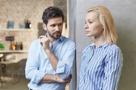Giovane coppia in piedi da muro a casa, donna in cerca gravi e ferito. Difficoltà di rapporto.