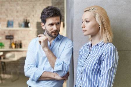 lovelorn: Young couple standing by wall at home, woman looking serious and hurt. Relationship difficulties. Stock Photo
