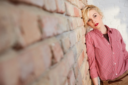 Young blonde woman daydreaming by brick wall. Stock Photo