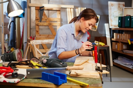 tinkering: Attractive woman tinkering in home workshop. Stock Photo
