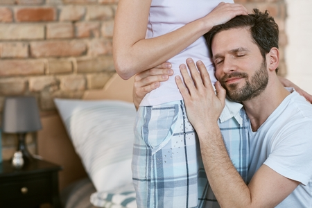 nightwear: Happy man hugging pregnant wife, listening and caressing her belly.