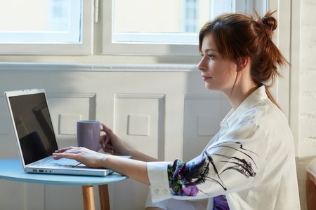 Young woman using laptop computer, sitting on floor.